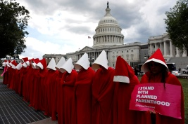 "REFILE - ADDITIONAL CAPTION INFORMATION Women dressed as handmaids from the novel, film and television series ""The Handmaid's Tale"" demonstrate against cuts for Planned Parenthood in the Republican Senate healthcare bill at the U.S. Capitol in Washington, U.S., June 27, 2017. REUTERS/Aaron P. Bernstein - RTS18W14"